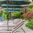 Stock Photo: Couches with umbrellas in garden