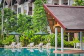 Couches with umbrellas around swimming pool — Stock Photo