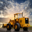 Yellow tractor on the road — Stock Photo