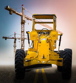 Old yellow motor grader on the road — Stock Photo