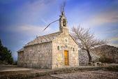Staré dalmatského kamene kostel s modrou oblohou — Stock fotografie