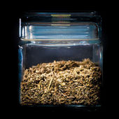 Homemade tea leaves in glass container — Stock Photo