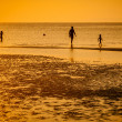 Familly on beach in orange sunset — Stock Photo