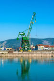 Large industrial crane in the river port with clear blue sky in the background. — Stock Photo