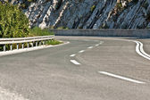 Curvy asphalt road with stone rocks in background. — Stock Photo
