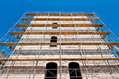 Old building during reconstruction with wooden scaffolding — Stock Photo