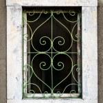 Rusty green metal window with decorative bars — Stock Photo