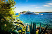 Luxury yacht anchored in a beautiful bay surrounded by greenery — Stock Photo