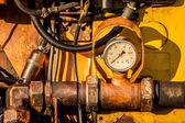 Close-up of dirty hydraulic machine with pressure clock. Horizon — Stock Photo