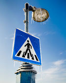 Frozen road sign for pedestrians with the street lamp above — Стоковое фото