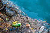 Water pollution old garbage and oil patches on river surface — Stock Photo
