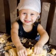 Child knead the dough in a kerchief - Stock Photo