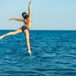 Girl in a free flying leap into the sea — Stock Photo