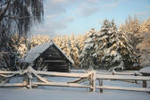 Wooden house in winter forest, sunset — Stock Photo