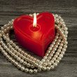 Red candle heart form and pearl necklace, Valentine's Day — Stock Photo