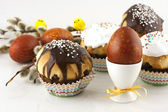 Easter eggs and tasty cupcakes with cream — Stock Photo
