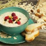 Oatmeal porridge with raspberry and raisins in a bowl — Stock Photo #41486325