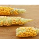Three corn cobs on a board. — Stock Photo #22000157