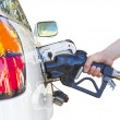 Stock Photo: Hand holding nozzle while fueling white car. Focus on nozz