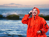 Man in storm cog talking on marine radio — Stock Photo