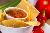 Red roasted tomato salsa with corn chips. — Stock Photo
