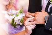 Brud klänningar en vigselring till brudgummen — Stockfoto