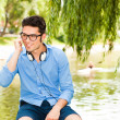 Handsome man standing on a bridge by the lake — Stock Photo #21437053