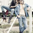 Foto Stock: Stylish couple wearing jeans and boots posing dramatic - retro processed image