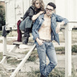Attractive fashionable couple wearing jeans posing dramatic - retro processed image — Stock Photo