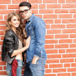 Stock Photo: Attractive fashionable couple casually leaning against brick wall