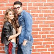 Attractive fashionable couple casually leaning against brick wall  — Stock Photo