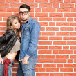 Attractive fashionable couple casually leaning against brick wall — Stock Photo #21435199