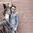 Foto Stock: Sexy and fashionable couple wearing jeans, shoot in grungy location - landscape orientation with copy-space