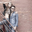 Sexy and fashionable couple wearing jeans, shoot in grungy location - landscape orientation with copy-space — Foto de stock #21435227
