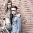Stock Photo: Sexy and fashionable couple wearing jeans, shoot in a grungy location - landscape orientation with copy-space