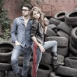 Stock fotografie: Sexy and fashionable couple wearing jeans, shoot in grungy location - landscape orientation with copy-space