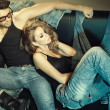 Sexy man and woman dressed in jeans doing a fashion photo shoot in a professional studio — Stock Photo