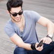 Attractive young male model playing games on a smart-phone — 图库照片