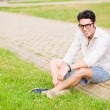 Handsome man wearing glasses sitting on the sidewalk and smiling — Stock Photo #21437187