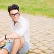 Handsome man wearing glasses sitting on the sidewalk smiling — Stock Photo #21437353