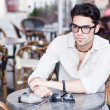 Attractive man wearing glasses standing at a terrace — Stock Photo #21437371