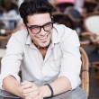 Attractive man wearing glasses standing at a terrace laughing — Stock Photo #21437403