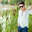 Handsome man wearing sunglasses standing by the lake — Stock Photo #21437453