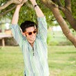 Handsome man wearing sunglasses smiling in the park — Stock Photo #21437573