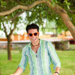 Handsome man wearing sunglasses having fun in the park — Stock Photo #21437629