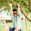 Handsome man wearing sunglasses having fun in the park — Stock Photo #21437637