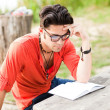 Student wearing glasses reading in the park — Stock Photo #21437749