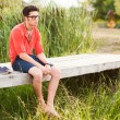 Handsome man standing on a bridge by the lake — Stock Photo
