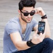 Stock Photo: Young male model making self portrait with smartphone