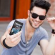 Young male model making self portrait with a smartphone — Stock Photo #21437885